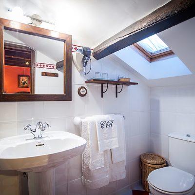 La luz cenital ilumina el cuarto de baño con techo abuhardillado